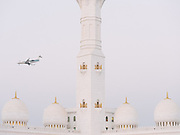 A passenger plane lands near the famous Sheikh Zayed Grand Mosque at sunset.
