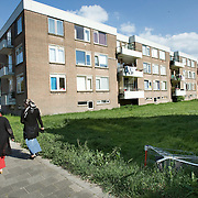 Nederland Rotterdam 01-06-2009 20090601 Foto: David Rozing   ..Achterstandswijk Pendrecht Rotterdam zuid, bewoners lopen door de wijk, op een grasveld is een winkelwagentje achtergelaten. Rommel laten slingeren.     deprived area / projects âEURoeKatendrecht âEURoe This area is on a list with projects which need help of the government because of degradation in the area etc., project, suburb, suburbian, problem. Neighboorhood, neighboorhoods, district, city, problems,  daily life Holland, The Netherlands, dutch, Pays Bas, Europe ..Foto: David Rozing/