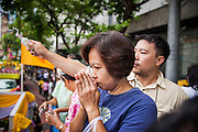 12 APRIL 2013 - BANGKOK, THAILAND: A Thai woman prays after sprinkling scented oils on the Phra Buddha Sihing on the first day of Songkran in Bangkok. The Phra Buddha Sihing, a revered statue of the Buddha, is carried by truck through the streets of Bangkok so people can make offerings and bathe it in scented oils. Songkran is celebrated in Thailand as the traditional New Year's Day from 13 to 16 April. The date of the festival was originally set by astrological calculation, but it is now fixed. If the days fall on a weekend, the missed days are taken on the weekdays immediately following. Songkran is in the hottest time of the year in Thailand, at the end of the dry season and provides an excuse for people to cool off in friendly water fights that take place throughout the country. The traditional Thai New Year has been a national holiday since 1940, when Thailand moved the first day of the year to January 1. The first day of the holiday period is generally the most devout and many people go to temples to make merit and offer prayers for the new year.  .  PHOTO BY JACK KURTZ