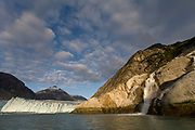 USA, Alaska, Tongass National Forest, Tracy Arm - Fords Terror Wilderness, Setting sun lights waterfall and Dawes Glacier in Endicott Arm