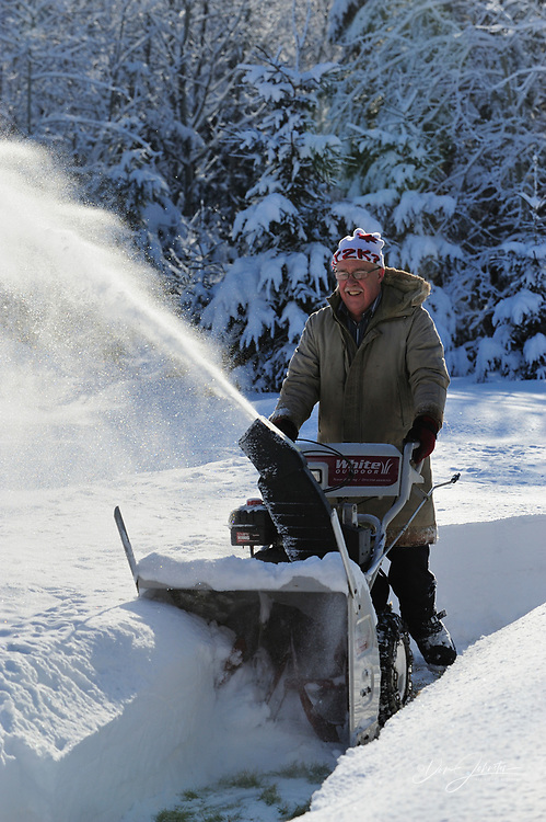 Man operating gasoline powered snow blower, Lively, Ontario, Canada