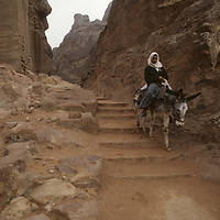 A Bedouin youngster rides a burro down ancient Nabataean steps above Petra, Jordan.