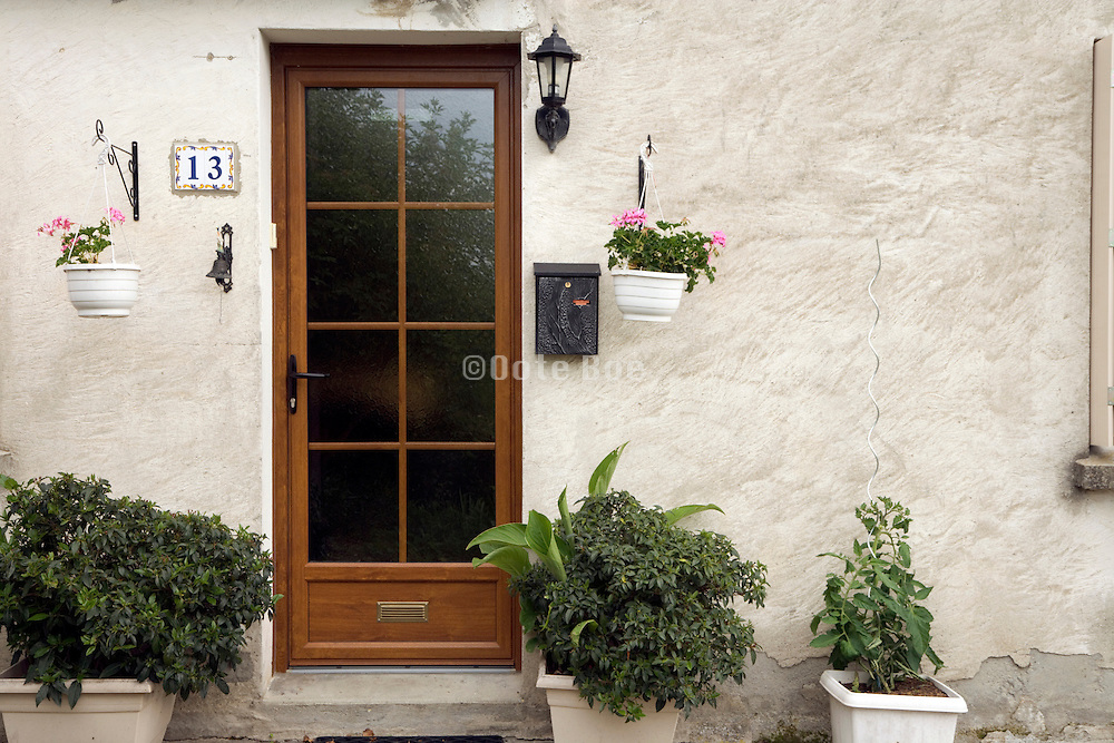 house number 13 with flower pots and front door