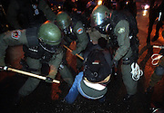 pvcteargas1/3-20-03/jp3/asec.  APD officers outfitted in full riot gear use their billy clubs on a youth that had joined about a half dozen other protestors in sitting down on Central Ave. SE near Buena Vista Dr. , as a group of several hundred protestors march East along Central, photographed Thursday March 20, 2003.  (Pat Vasquez-Cunningham/Journal)