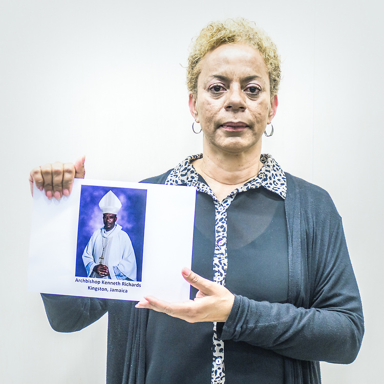 2018<br /> Denise Buchanan, a victim and an activist from Jamaica, poses for a portrait showing a picture of the Archbishop of Kingston Kenneth Richards who allows the priest that abused and make her pregnant, to still be in ministry. © Simone Padovani