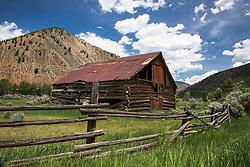 Old log barn with it's old pole fence decorating the landscape in Clayton Idaho