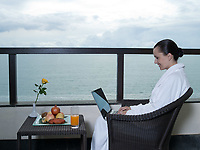 beautiful calm and serene woman in palace hotel room at the balcony facing the sea with a computer laptot