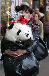 © Licensed to London News Pictures. 19/12/2015. London, UK. A shopper carries a giant Panda toy in Oxford Street on the last Saturday before Christmas. Photo credit: Peter Macdiarmid/LNP