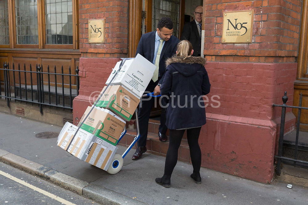 A male employee of a Barristers helps a woman colleague with a boxes of legal documents into the chambers address in the City of London, the capitals financial district, on 25th March 2019, in London, England.