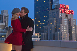 couple on a rooftop overlooking the New Yorker Hotel and Midtown Manhattan