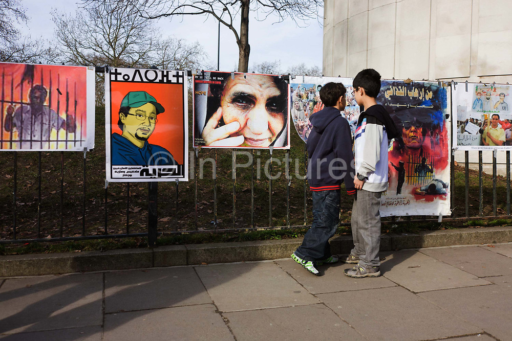 Young boys look at graphic posters as Libyan exiles protest opposite their London embassy. The young lads look at the display of printed images that have been attached to railings opposite their country's embassy in London's Knightsbridge. The political protest is against their long-term dictator Muammar al-Gaddafi whose violence has led to a nationwide uprising though these boys are exiled in Britain with their families.