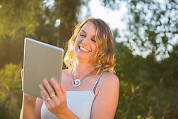 Cheerful woman smiling while using digital tablet outdoor in nature, Bavaria, Germany