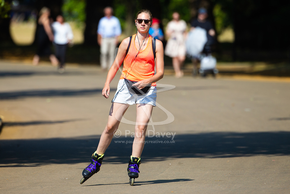 A woman glides past The Serpentine on her rollerblades in Hyde Park as another heatwave day begins with temperatures expected to soar. London, July 01 2018.