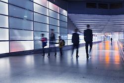 Passengers walking in illuminated passageway in Interior of Potsdamer Platz railway station in Berlin Germany