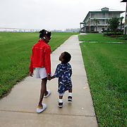 WEST PALM BEACH, FL - September 6, 2005:  My-Shelle Johnson, 8, walks at a evacuation shelter with her little brother, Kevin Johnson the 5th, 2 yrs, on Sept 6, 2005 in West Palm Beach, Florida. The shelter is called Palm Meadows and is a training facility for thoroughbred horses. The Johnson family evacuated New Orleans after being stranded for days in their flooded home and having to watch dead bodies float by. (Photo by Todd Bigelow/Aurora)
