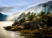 """A dramatic capture of a rocky promentory silhouetted against rainy mists running up distant mountain sides on the British Columbia coast. """"South of Squamish"""", epitomizes the British Columbian coast. The hillsides, conifer groves, rocky promontories, the sea-level fog clouds that, blown by the breeze, rain their way up the hillside to become mist. There might be superior depictions but not by much.<br /> South of Squamish has won 'best in show' bestowed by a judging panel with genuine credentials. It has also been dismissed, on two separate occasions, by jurors who deemed it: """"Photoshopped""""! Apparently too good to be true. Yet minimal post processing has been applied. This is the real deal.<br /> What is going on here? Photojournalism contests are widely reported wherein artistic merit is subordinate and verbatim reportage paramount. The trick is to deliver aesthetically pleasing images without any compromise whatsoever to journalistic principles. No cloning! No artistic licence! No editorializing. Verbatim reportage or nothing. In advertising and similar gendres, verbatim rules justly apply. Photography, beyond such circumscribed specialties, is exempt from such rules just as painters, sculptors and others are. No painter has ever been accused of """"paintshopping"""" tourists, or anything else for that matter, in or out of a scene. <br /> Camera-based art is as legitimate as paint-brush based art. It is irrelevant how it got there.<br /> South of Squamish has been the victim of ignorance and incompetence."""