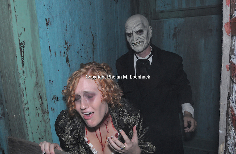 A ghoul slashes the throat of a woman in the Body Collectors: Collections of the Past venue during a dress rehearsal of Universal Studios Florida's Halloween Horror Nights in Orlando, Fla., Tuesday, Sept. 16, 2008.