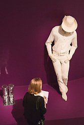 """© Licensed to London News Pictures. 21/10/2013. London, England. A visitor stands in front of the figure of a large white cowboy. The Exhibition """"Pop Art Design"""" opens at the Barbican Art Gallery/Barbican Centre running from 22 October 2013 to 9 February 2014. The exhibition brings together 200 works by 70 artists and designers including Peter Blake, Andy Warhol and Roy Lichtenstein. Photo credit: Bettina Strenske/LNP"""