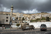 An Israeli armored vehicle and a jeep are stationed in the main road of<br /> the West Bank town of Nablus to subdue an angry mob of Palestinian youths who threw rocks in protest of the enforced curfew. IDF (Israeli Defense Force) responded the rioters with tear gas and rubber bullets at the youths. IDF said it enforced the curfew to conduct a military operation and find the terrorists.