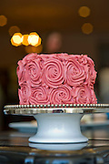 A cake covered in pink roses in a bakery at Meridienne Dessert Salon and Cafe in Rogers, Arkansas.
