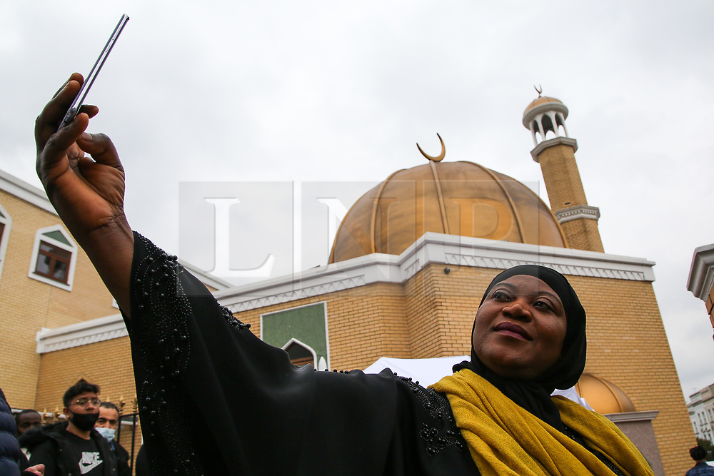 © Licensed to London News Pictures. 13/05/2021. London, UK. A muslim woman takes a selfie outside London Islamic Cultural Society and Mosque, also known as Wightman Road Mosque in north London. Eid al-Fitr or the 'Festival of Breaking the Fast' celebrates the end of the month-long fast of Ramadan, and is being celebrated differently this year as a result of the coronavirus (COVID-19) pandemic. Prime Minister Boris Johnson announced that Covid-19 restrictions on social gatherings, meeting indoors and social contact will ease on May 17, meaning Eid celebrations this week still face restrictions.   Photo credit: Dinendra Haria/LNP