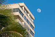 The moon next to a building and palm trees in Honolulu, Hawaii.