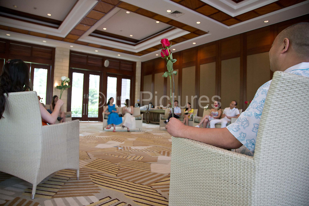 Participants of Diamond Love, a high-end dating service, attends a wrap meeting where they use roses to express their interests in someone, in Sanya, Hainan Province,  China on15 June  2013.  Male participants of the dating service pay up to 20,000 USD to attend such events in hopes of finding a suitable match while most of the women are selected by the match making service according to their looks, education, and personality.