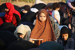 June 15, 2018 - Gaza City, Gaza Strip - Palestinian Muslim worshipers perform Eid al-Fitr prayer at Israel-Gaza border in east of Gaza city on June 15, 2018. Eid al-Fitr marks the end of Muslim's holy fasting month of Ramadan when faithfuls abstain from eating, drinking, smoking and sexual activities from dawn to dusk  (Credit Image: © Mahmoud Ajour/APA Images via ZUMA Wire)