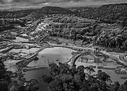 """Saint-Elie, Guyane, 2015.<br /> <br /> Saint-Elie est un des plus anciens villages de l'intérieur guyanais, créé par l'orpaillage au XIXe siècle. Pratiquement déserté et très fortement enclavé, Saint-Élie a connu sa période de gloire avec la saga de l'orpaillage illégale au début des années 2000. Plusieurs centaines de clandestins Brésiliens s'y installent. Le bourg devient hors de contrôle. En 2008, l'opération Harpie menée par les Forces Armées en Guyane oblige les clandestins à quitter les lieux et 22 commerçants de Saint-Élie sont appelés à comparaître pour complicité d'orpaillage illégal. Saint-Élie devient un village fantôme avec ses 38 électeurs inscrits mais installés pour la large majorité sur le littoral guyanais. De fait une dizaine de personnes vivent aujourd'hui sur place : cinq gendarmes mobiles qui se relaient toutes les deux semaines et veillent à ce qu'aucun clandestin ne s'installe, au moins deux agents municipaux permanents, un brésilien et un unique commerçant qui attend le retour des clandestins. Si le territoire de la commune s'étend sur 5680 km2, le bourg de Saint-Elie bâti à flanc de colline et assoupi sur un gisement d'or n'est plus propriétaire de l'intégralité de son foncier. Le village est maintenant cerné par des opérateurs miniers légaux.<br /> <br /> Le village reste pratiquement inaccessible par des moyens légaux. En l'absence de  piste d'atterrissage pour les  avions, on ne s'y rend qu'en hélicoptère, ou alors depuis la route nationale du littoral, en empruntant un chemin de 27 km tracé dans la forêt, (en principe seulement autorisé aux agent EDF), jusqu'au barrage de Petit-Saut. Il faut un canot pour traverser le lac de retenue du barrage jusqu'au débarcadère du PK6 après une heure et demie de navigation et terminer en 4×4 26 km de piste, ce trajet par la """"route"""" peut durer de 6 heures à 2 jours selon la saison."""