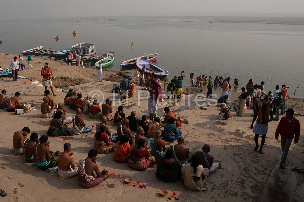 People worshipping and bathing in the river ganges at dawn on 21st December 2009, Varanasi / Benares, Uttar Pradesh, India. According to Hindu mythology, Varanasi was founded by Shiva, one of three principal deities along with Brahma and Vishnu, and is seen as a significant and holy place to followers of the Hundu faith.