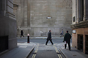 Lunchtime pedestrians on the corner of Lothbury and Tokenhouse Yard, two narrow and historic streets with the high walls of the Bank of England in the background - in the City of London, the capital's financial district. The area was populated with coppersmiths in the Middle Ages before later becoming home to a number of merchants and bankers. Lothbury borders the Bank of England on the building's northern side. Tokenhouse St dates from Charles I and was where farthing tokens were coined. The City of London is the capital's historic centre first occupied by the Romans then expanded during following centuries until today, it has a resident population of under 10,000 but a daily working population of 311,000.