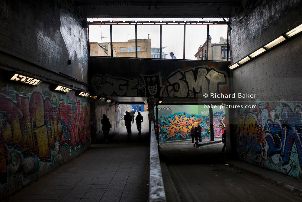 Sinister silhouettes in underpass tunnel with walls covered with urban graffiti.