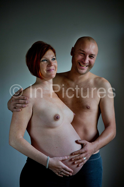 30 year old pregnant woman, (8 months), with her partner, showing the bulging stomach lit by the morning light through her appartment window.