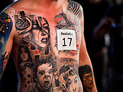 28 OCTOBER 2018 - BANGKOK, THAILAND: A man stands on stage with his tattoos during judging of the Realistic division at the 2018 MBK Center Tattoo Fest. Tatoo artists from around the world came to participate in the festival, which featured both modern (using tattoo machines) and traditional methods (done by hand with long needles) of tattooing.  PHOTO BY JACK KURTZ