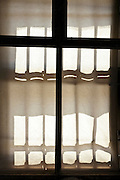strong sunlight projection of an old style metal grating on curtain screen outside of the window