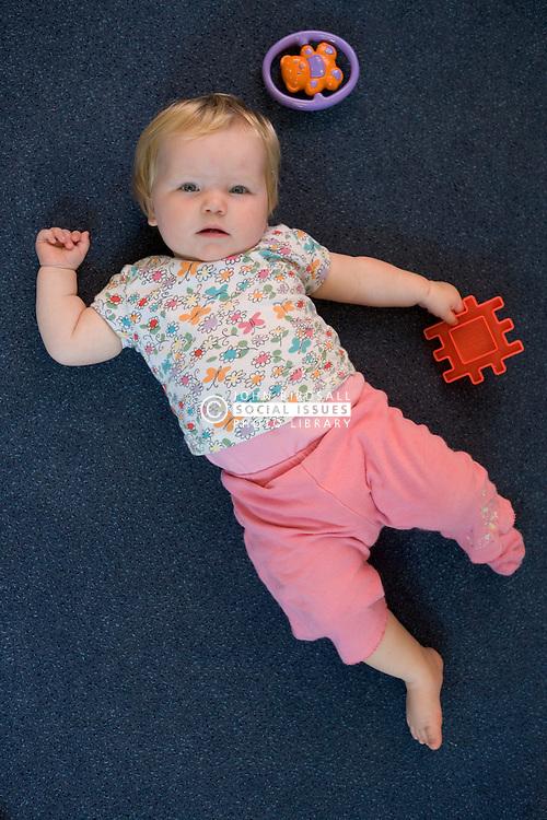 Baby at Nursery School; lying on the floor,