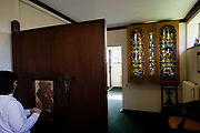 A Catholic confessional between a penitent parishioner and her local priest at St. Lawrence's Catholic church in Feltham, London. While kneeling to face the priest, the lady speaks in absolute confidence and secrecy to a screen beyond which the man listens and offers spiritual advice. A confessional is a small, enclosed booth used for the Sacrament of Penance, often called confession, or Reconciliation. Usually, the priest and penitent are in separate compartments and speak to each other through a grid or lattice and a crucifix hangs over the grille. But here, a screen grille inserted in it separates the two. The penitent may be able to see the priest through the screen, but the priest can usually never see the penitent - hearing instead of the person's sinful admissions.