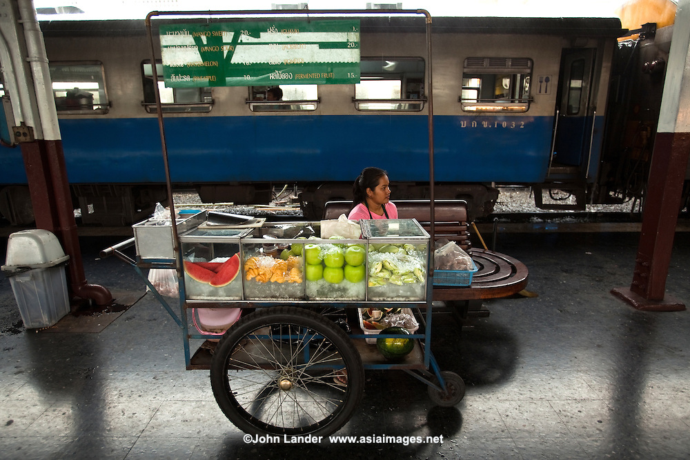 Bangkok Railway Station Hualaphong platform Vendor, catering to long-distance train travelers with fresh fruit, barbequed chicken, chips and snacks.