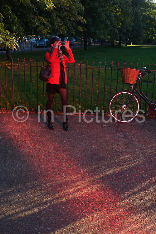 Red-tinted landscape with lady wearing red caused by the Serpentine Gallery's Pavilion. With a stripe of vivid red shining across the pavement of one of London's most eminent of green spaces, a lady pauses to photograph the unseen pavilion in late afternoon light, her coat matching the hues produced by light passing through the building. The Serpentine's 40th Anniversary—the Serpentine Gallery Pavilion is designed by world-renowned French architect Jean Nouvel. The entire design is rendered in a vivid red that, in a play of opposites, contrasts with the green of its park setting. In London, the colour reflects the iconic British images of traditional telephone boxes, post boxes and London buses. The building consists of bold geometric forms, large retractable awnings and a sloped freestanding wall that stands 12m above the lawn.