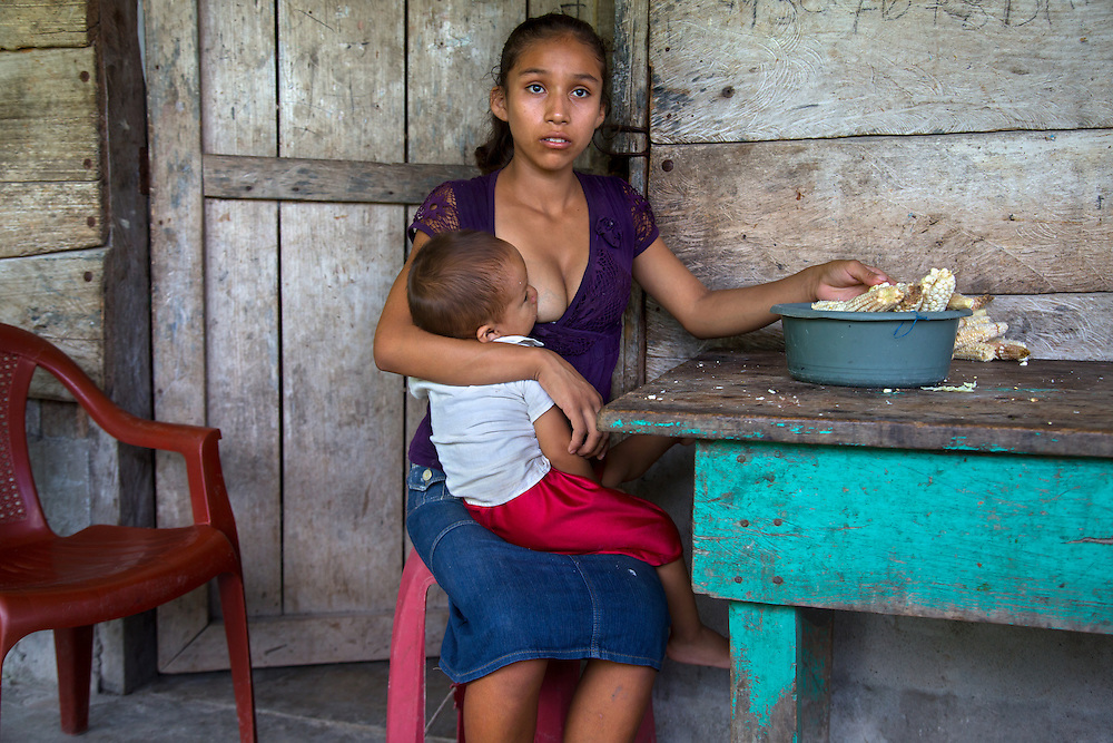"""Aracely, 15, holds her infant. """"What I hope is to keep moving forward... to see how I can get my boy ahead. The hard thing, maybe... when he gets older and he leaves... that's when is going to be hard for me. When he is older. Because he is the one who will help me get ahead.<br /> <br /> Aracely is one of the half a million of Guatemalan girls who marry and give birth before they can legally vote, drink, or buy cigarettes. According to a 2012 UN Population Fund survey, 30% of Guatemalan women aged 20-24 were married by 18, and that number may be even higher in rural areas. Teenage births are so common that there's even a law requiring mothers under 14 to have C-sections, because their hips are too narrow to give birth."""