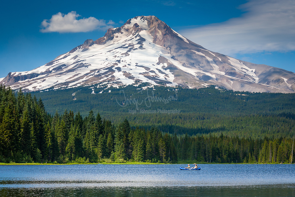 Trillium Lake south of Mount Hood with view of the mountain, two people in a canoe on the lake