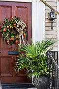 A traditional low country Christmas wreath decorated with fruit hangs from a wooden door on a historic home along King Street in Charleston, SC.
