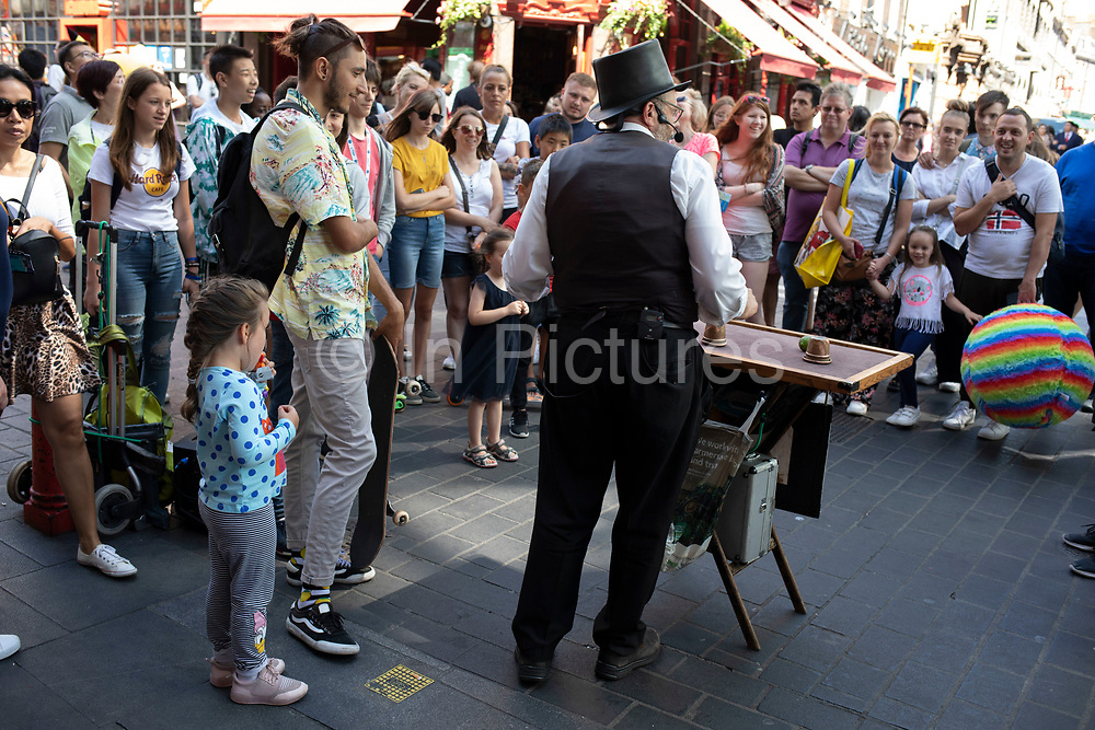 Street scene as a crowd of tourists of all ages gather to watch a street magic show by a street performer / busker wearing a waitcoat and a top hat in Chinatown in Soho, London, United Kingdom. The present Chinatown is in the Soho area occupying the area in and around Gerrard Street. It contains a number of Chinese restaurants, bakeries, supermarkets, souvenir shops, and other Chinese-run businesses and is in itself a major tourist destination.