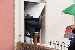 """© Licensed to London News Pictures.09/04/2016. Bristol, UK.  Protesters stop the door being closed by viewing agents and enter a property to stop viewings of council houses for auction in City Road, St Pauls, Bristol. Campaigners want the council to stop selling off 15 council homes on 20 April by auction to the private sector. Bristol City Council says the homes are expensive to repair, but some campaigners question whether the costs of repairs are inflated, and also whether the homes will be bought and then relet to the Council for temporary accommodation at higher than normal rents. Bristol resident Roger Yates said: """"The idea the Council can't afford to do these places up is piffle. All over Bristol folk are improving property to increase its value on a rising housing market. These are valuable assets. But Ferguson (Bristol's elected mayor) wants to socially cleanse inner city Bristol so that his luvvie mates can move in. The poor will relocate to Hartcliffe or the street."""" A group of residents of St. Paul's and the Inner City are working together to put pressure on BCC to stop the sale. They are working in partnership with The Community Rights Project, The Bristol People's Assembly, and members of the ACORN community union. Photo credit : Simon Chapman/LNP"""