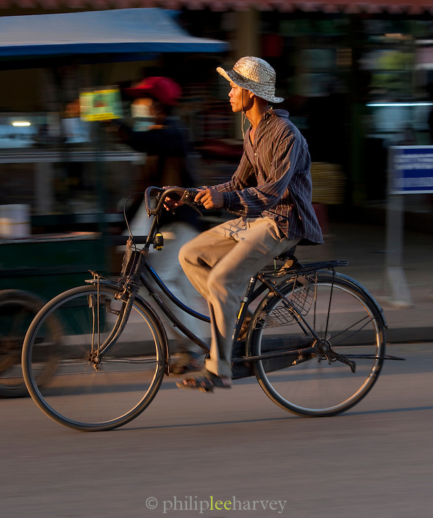 A man cycles through the streets of Siem Reap, Cambodia