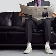 Early 30's caucasian male wearing a slim tailored suit, reading a newspaper while sitting on a black leather couch.