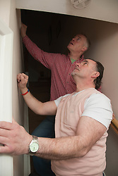 Housing officer with tenant inspecting stairs.