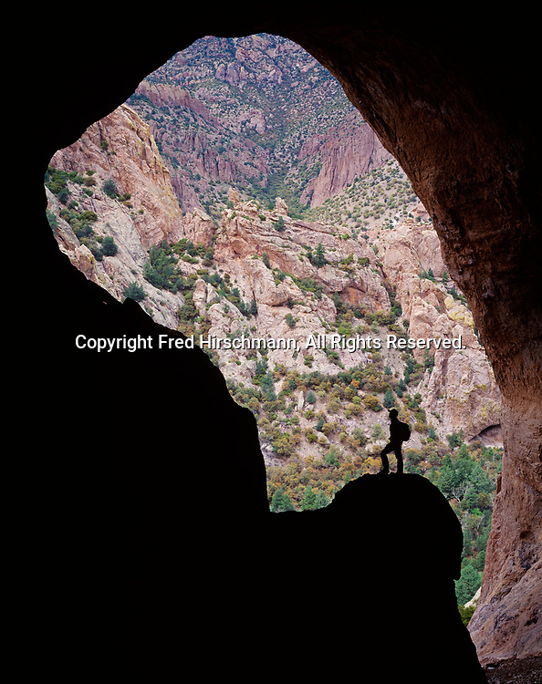 Jennifer Whipple silhouetted in opening of large cave above Cave Creek framing rocky slopes of the Chiricahua Mountains, Cave Creek Recreation Area, Coronado National Forest, Arizona.