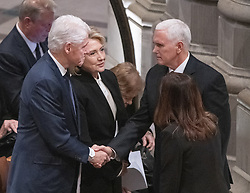 Former United States President Bill Clinton, left, shakes hands with US Vice President Mike Pence, left, as former US Secretary of State Hillary Rodham Clinton, center, looks on prior to the start of the National funeral service in honor of the late former United States President George H.W. Bush at the Washington National Cathedral in Washington, DC on Wednesday, December 5, 2018.<br /> Photo by Ron Sachs / CNP/ABACAPRESS.COM