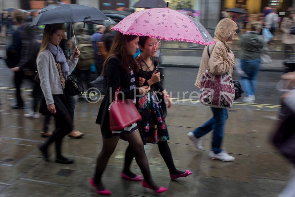 Londoners walk along central London's Oxford Street during autumnal rain. Wearing matching pink shoes and with one lady carrying a pink umbrella, two women walk and talk in the rain shower, on a damp pavement in the capital's West End - a centre for retail whose business is is under threat by covered malls elsewhere. The crowds have flocked to this old street, once the route for criminals towards the Tyburn gallows.